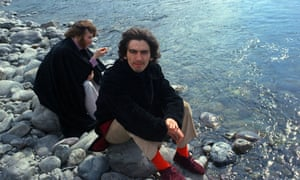 George Harrison and John Lennon sit on rocks by a river in Rishikesh while studying transcendental meditation.