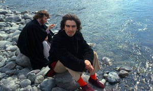 John Lennon and George Harrison sit by a river in Rishikesh, India, in 1968.