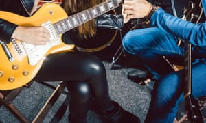 Guitar music teacher helping his student