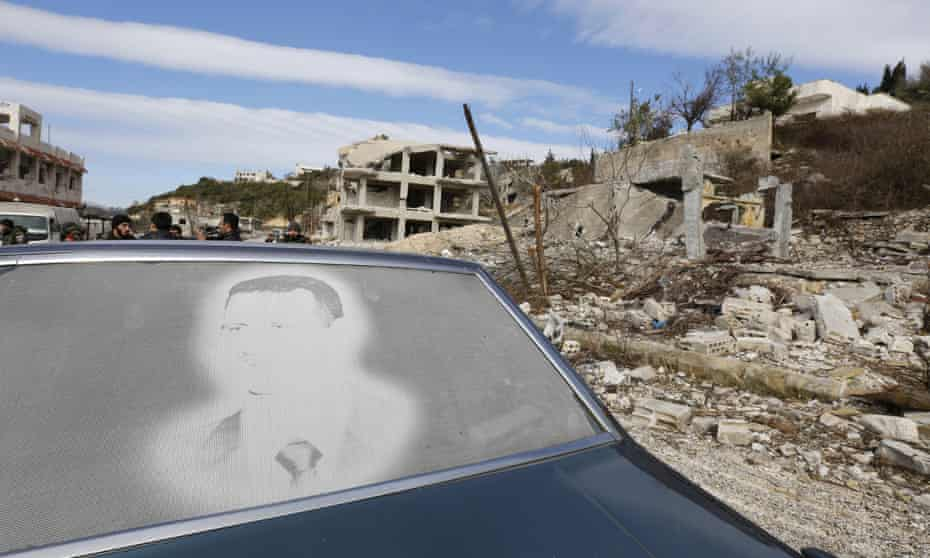 An image of Bashar al-Assad is seen on a car parked in front of damaged buildings in the town of Rabiya, Syria