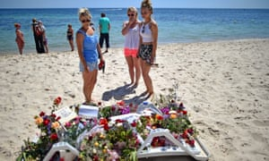 Holidaymakers view flowers left on Marhaba beach in Sousse.