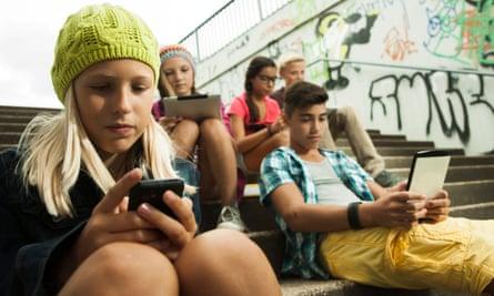 Children using mobile phones in school