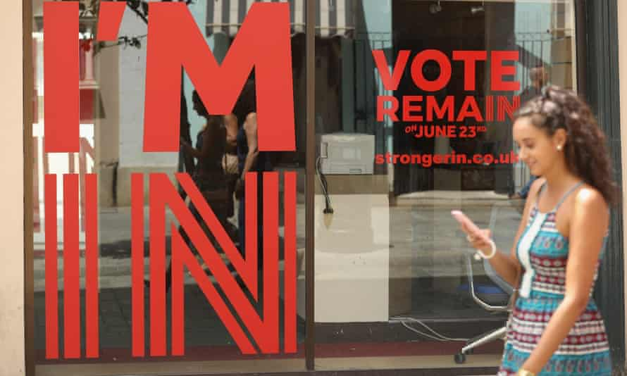 A young woman walks past a Gibraltar storefront sign urging people to vote to remain.