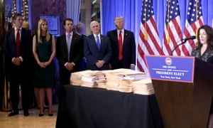 Donald Trump, accompanied by Mike Pence and family members stands behind piles of documents purportedly detailing his actions to divest himself of his business interests.