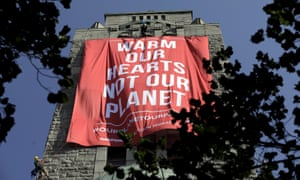 Members of the environmental group Greenpeace place a banner on the tower of the Kallio Church as they protest against Donald Trump's visit in Helsinki.