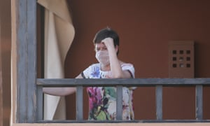 A woman wearing a face mask looks out from the H10 Costa Adeje Palace hotel in La Caleta, in the Canary Island of Tenerife, Spain, Friday Feb. 28, 2020. Some guests have started to leave the locked down hotel after undergoing screening for the new virus that is infecting hundreds worldwide.