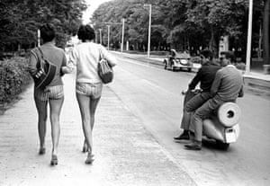 Men on a scooter ogle women walking on a street
