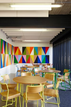 Colourful walls and wooden chairs around circular wooden tables