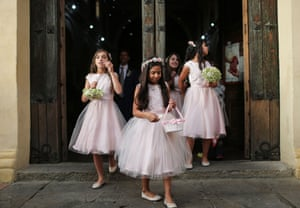 A flower girl blows bubbles as a wedding party departs a church in Bogota, Colombia
