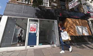 A woman walks past two closed businesses on Upper Street in Islington, north London