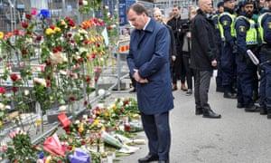 Swedish prime minister Stefan Löfven looks at flowers as he visits the crime scene in central Stockholm.