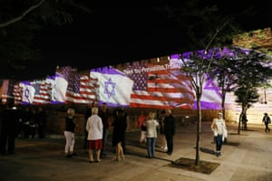 People take photographs of the US and Israeli flags projected as a show of unity on to the walls surrounding Jerusalem's Old City