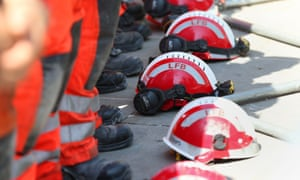 Firefighters lay their helmets on the ground as they observe a minute's silence after the Grenfell Tower fire