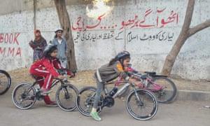 The Lyari girls cycle past graffiti.
