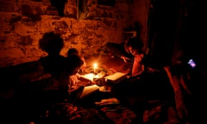 Palestinian children do their homework during a power cut in an impoverished part of Gaza City