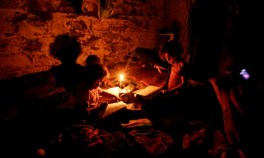 Palestinian children do their homework during a power cut in Gaza City