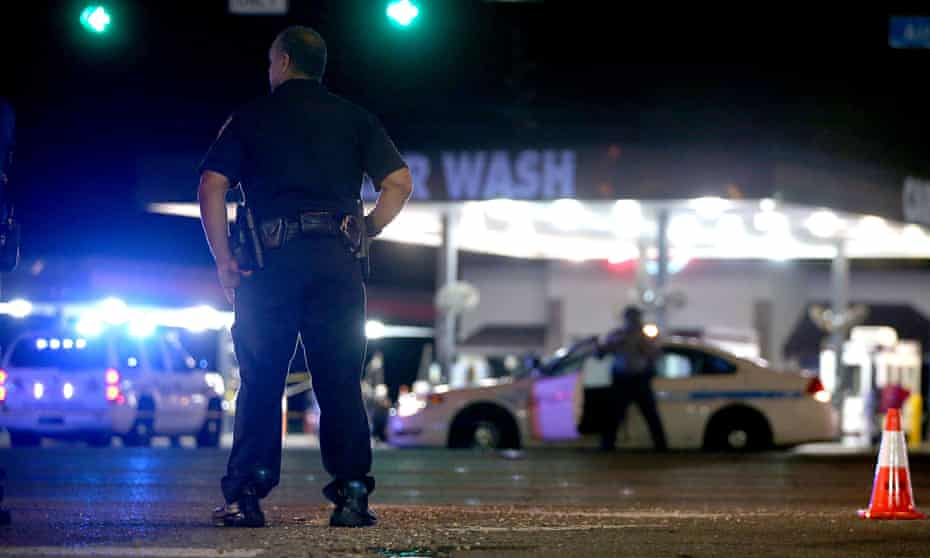 Police officers stand near the scene of where three police officers were killed in Baton Rouge, Louisiana.