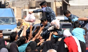 Iraqi security forces distribute food to people in need during curfew due to coronavirus pandemic in Baghdad
