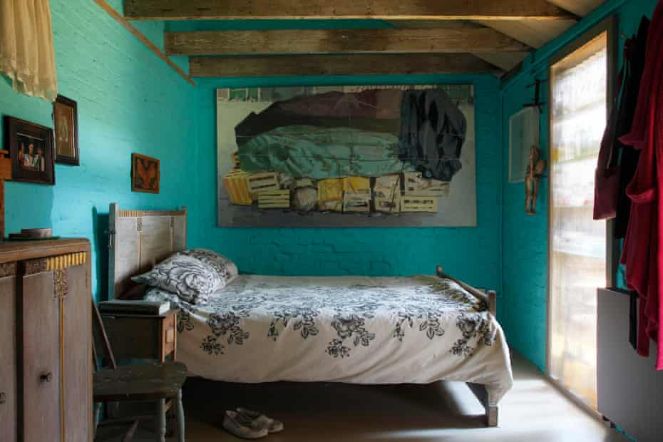 The bedroom, with its almost luminous turquoise walls and 30s bed.