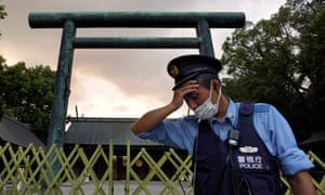 A policeman wipes sweat from his forehead while on duty in the summer heat in front of a Torii gate at the Yasukuni Shrine in Tokyo, Japan, in August.