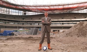 Arsène Wenger stands on the centre spot of the Emirates Stadium during construction in 2005. He was fundamental to the building of the modern, lucrative new ground.
