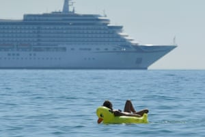 People cool off in the sea of Bournemouth with the cruise ship Arcadia anchored in the background
