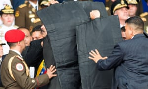 Security agents respond to a claimed assassination attempt on President Maduro, who is partly visible behind protective screen.