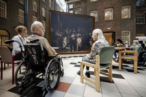 Residents of the Dr Sarphati House nursing home sit in front of a same size reproduction of the famous painting The Night Watch by Dutch painter Rembrandt van Rijn.