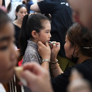 A young model has make-up applied at a contest