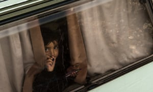 A young girl draws with a crayon on the window of a trailer at the migrant camp known as the jungle in Calais.