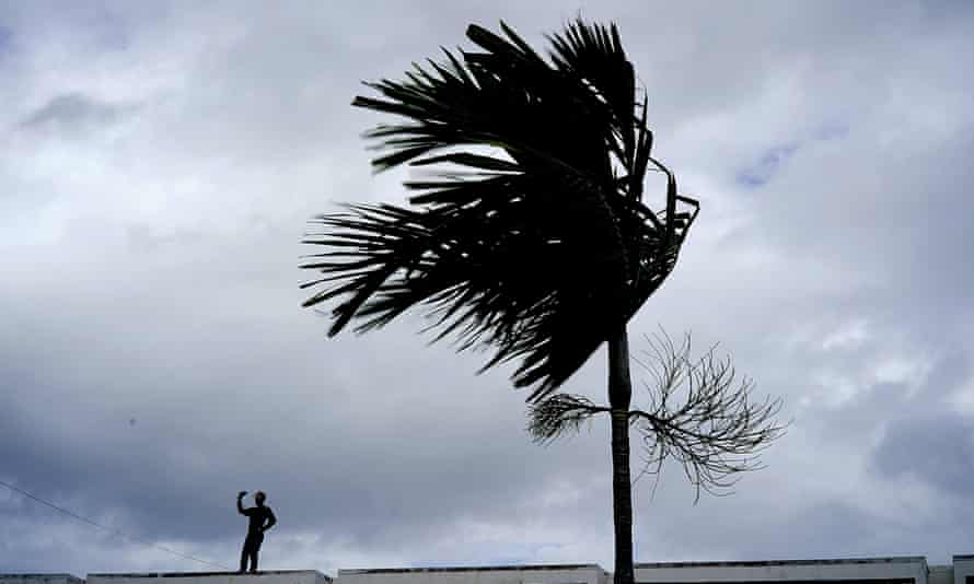 A man stands on a store's roof as he works to prepare it for the arrival of Hurricane Dorian in Freeport on Grand Bahama, Bahamas, on 1 September.