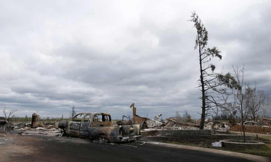 A charred vehicle and homes are pictured in the Beacon Hill neighbourhood of Fort McMurray, Alberta, Canada, May 9, 2016 after wildfires forced the evacuation of the town.