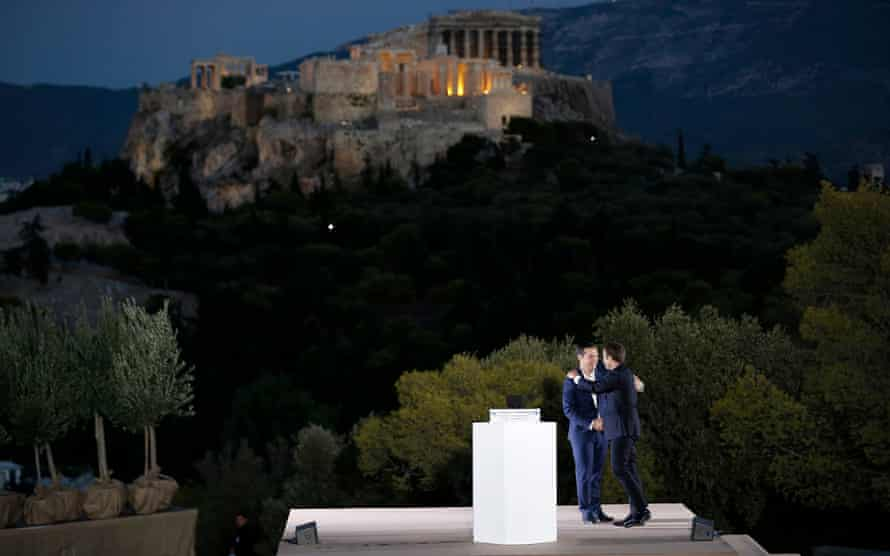 Greek prime minister Alexis Tsipras hugs French president Emmanuel Macron after delivering a speech atop the Pnyx hill.