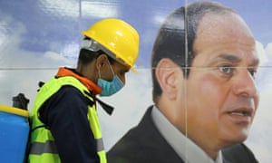 A man sprays disinfectant on a street in Cairo, by a banner of Egyptian president Abdel Fatah al-Sisi.