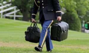 A military aide carries the nuclear football.