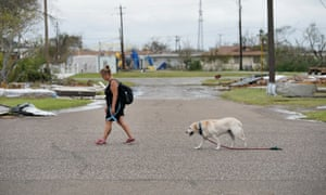A local resident and her dog walk home in Houston in the aftermath of Hurricane Harvey, the strongest to hit the US since 2005.