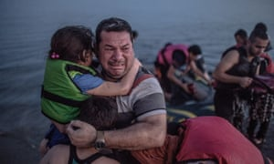 Safe landing: Laith Majid from Deir Ezzor in Syria, holding his son and daughter, breaks out in tears of joy after arriving via a flimsy inflatable boat crammed with about 15 men, women and children on the shore of the island of Kos in Greece.