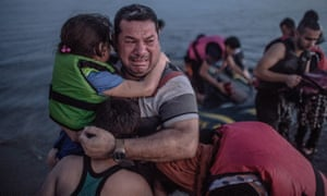 Laith Majid, a Syrian refugee, holding his son and daughter, arriving on the Greek island of Kos in August.