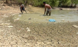 Cambodian men use a net to catch fish in a nearly dried pond at a village in Kandal province.