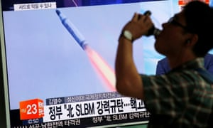 A man in Seoul walks past a TV screen broadcasting a news report on North Korea's submarine-launched ballistic missile fired from North Korea's east coast port of Sinpo.