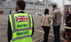 Man wears British embassy vest at the ferry terminal at Santander, Spain.