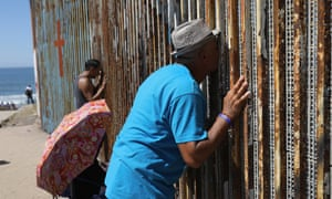 A Mexican who was deported from the US kisses his wife through the border fence in Tijuana