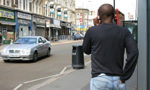 A man using a mobile phone while walking down a street