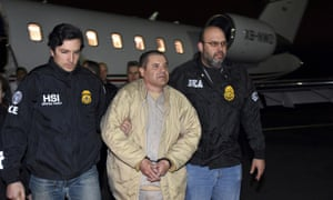 In this January 2017 file photo, authorities escort Joaquín 'El Chapo' Guzmán, center, from a plane to a waiting caravan of SUVs at Long Island MacArthur Airport, in New York.