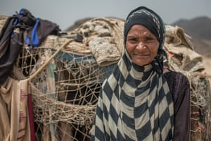 Samira stands before her temporary home in Ras Imran