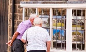 An elderly couple looking in an Estate Agents window