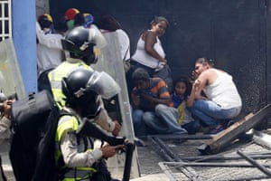 Anti-government demonstrators take cover from the Bolivarian Police officers