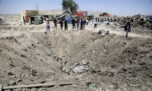 Afghan security officials inspect the site of the truck bomb blast in Kabul