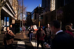Pedestrians walk past the tent city in the CBD