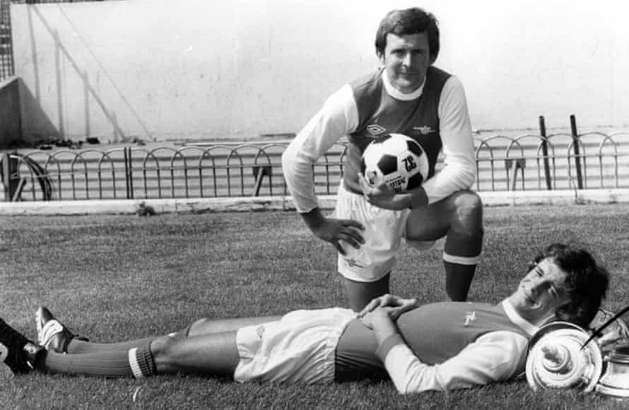 Arsenal's new signing John Hollins poses for the camera at Highbury whilst David O'Leary puts the handily shaped FA Cup to good use as he has a rest.